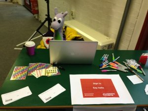 Puffles at the welcome desk for CommsCamp13 - with stickers for everyone