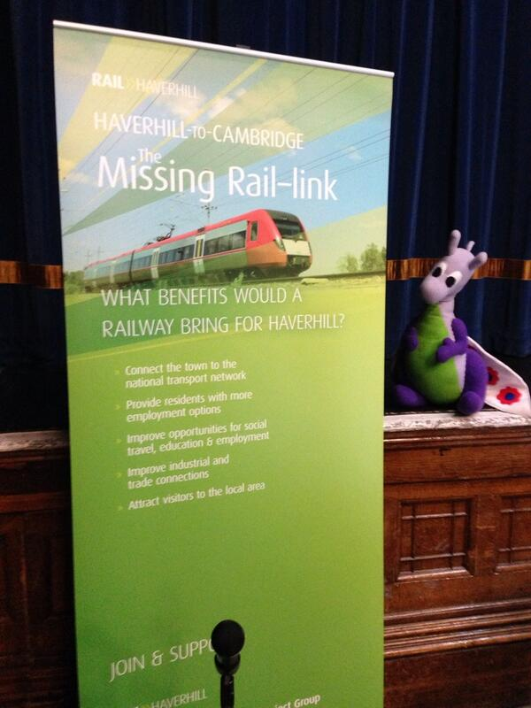 Puffles at Haverhill Arts Centre with a banner for the Haverhill-Cambridge Rail Campaign